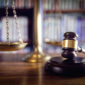 Judge gavel, scales of justice and law books in court
